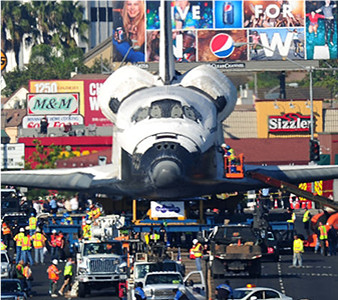 Space shuttle going down the street in a parade